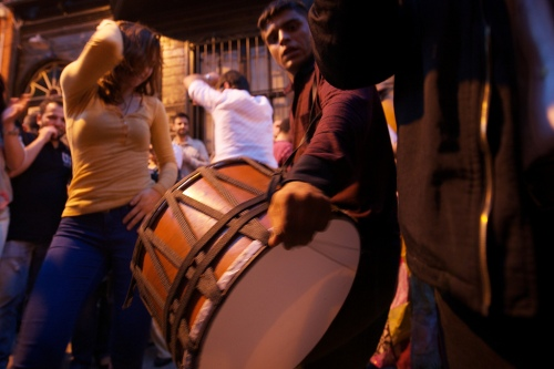 A man plays his drum entertaining a girl dancing around him